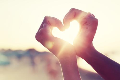 Herz aus Händen vor Sonnenuntergang